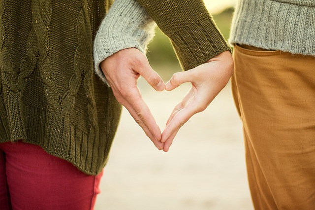 a couple holding hands and making the love heart symbol