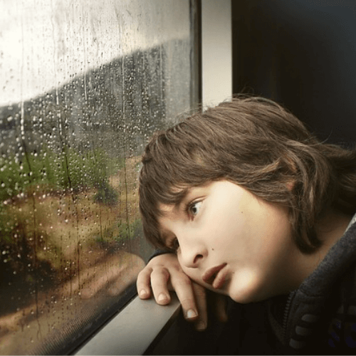 a young boy looking out of the rainy window who is not getting enough vitamin d