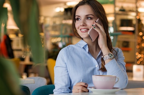 a young lady on the phone in a coffee shop drinking a cup of tisanes tea