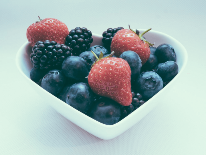 strawberries, blackberries and blueberries in a heart shaped bowl