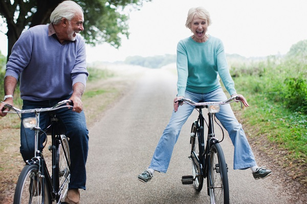 elderly couple riding bicycles and laughing