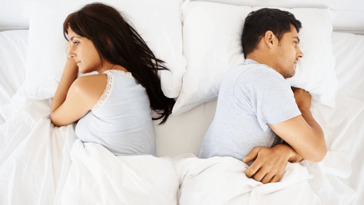 a couple in bed with erectile dysfunction problems