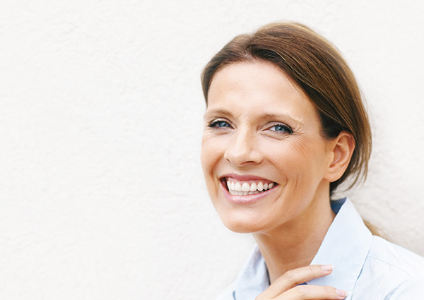 Portrait of a smiling business woman leaning against a wall