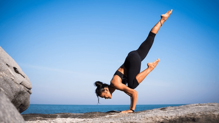 A lady holding a very strong yoga pose by the ocean to improve her health and wellbeing