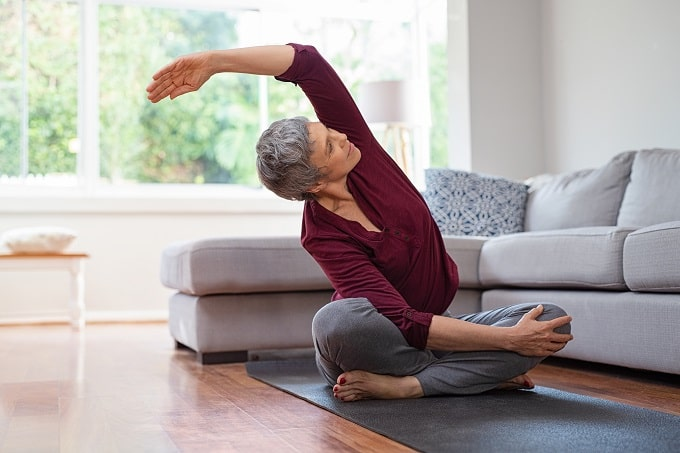Woman stretching and doing yoga to prevent joint and muscle ache caused by menopause